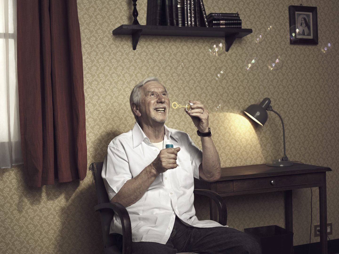 Old man making soap bubbles in room 42 by Stefan Rappo