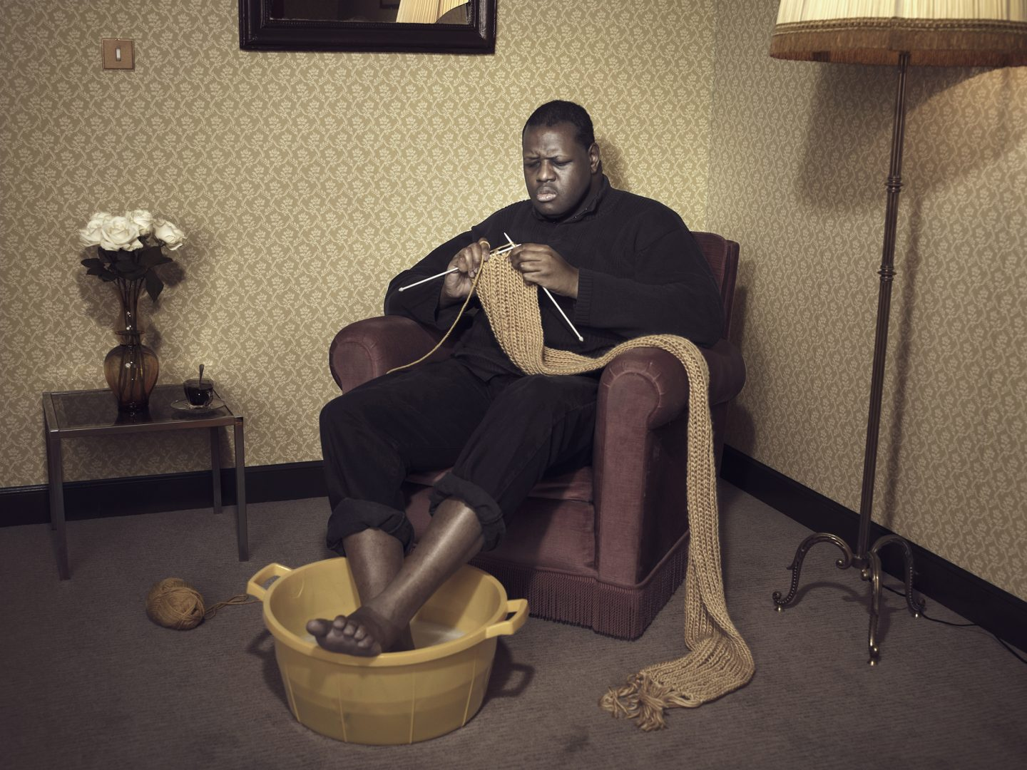 Black man sitting in armchair and knitting in room 42 by Stefan Rappo