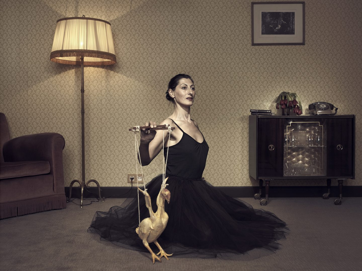 Woman playing with chicken in room 42 by Stefan Rappo