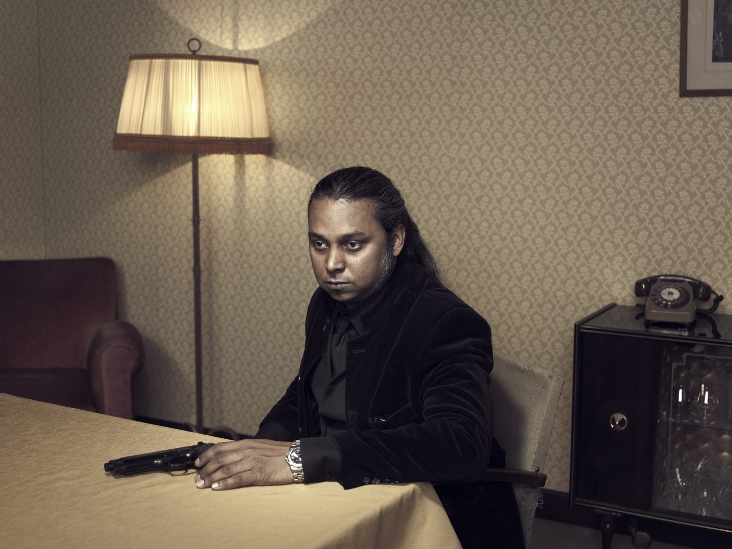 Man with gun sitting at table in room 42 by Stefan Rappo