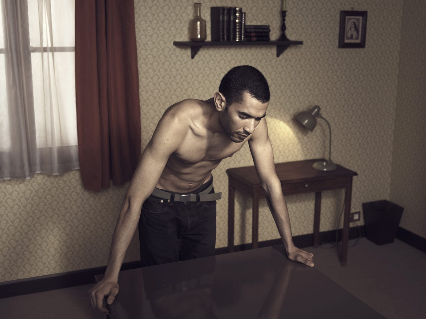 Man leaning on table in room 42 by Stefan Rappo