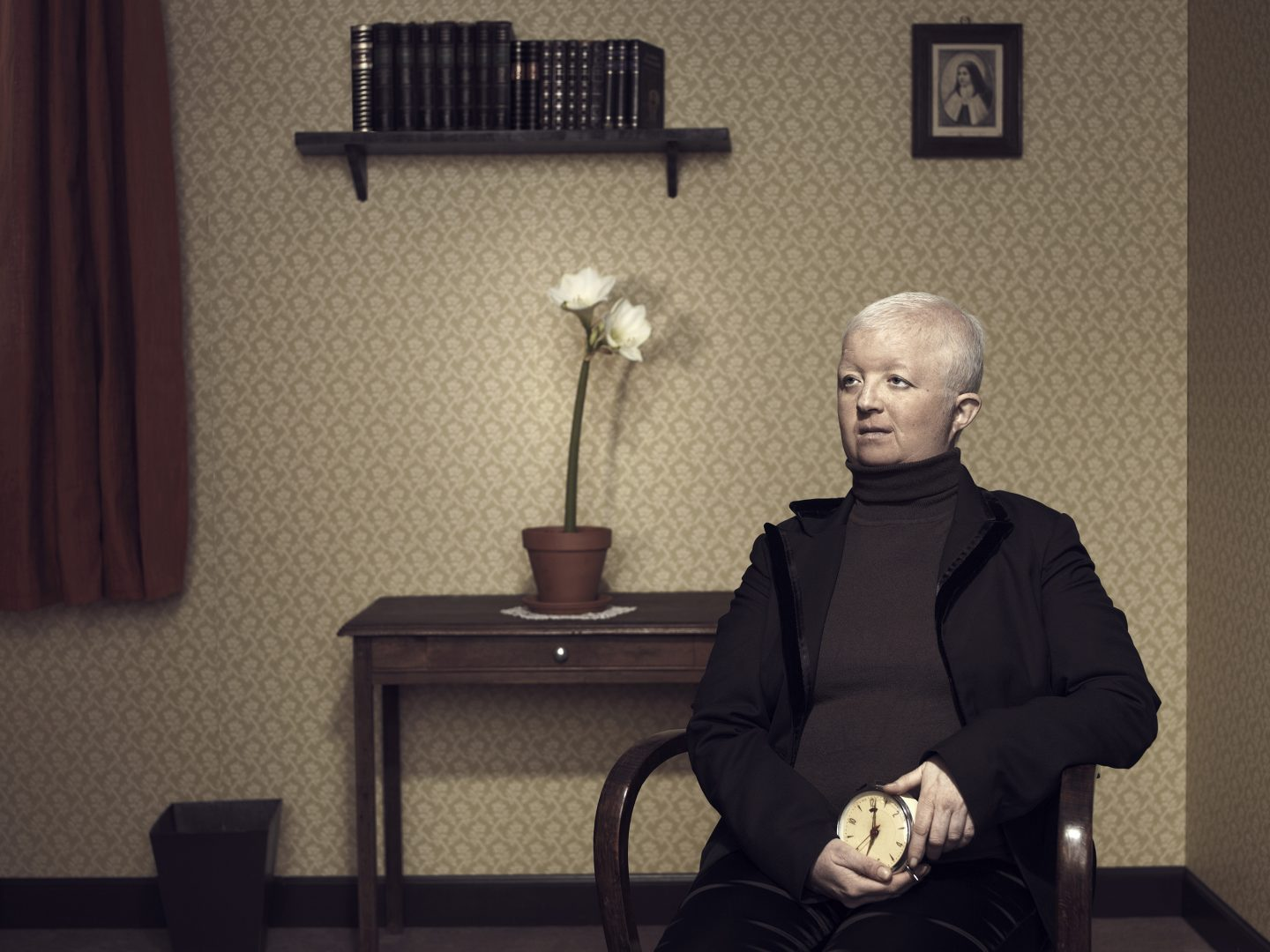 Woman with alarm clock sitting on chair in room 42 by Stefan Rappo