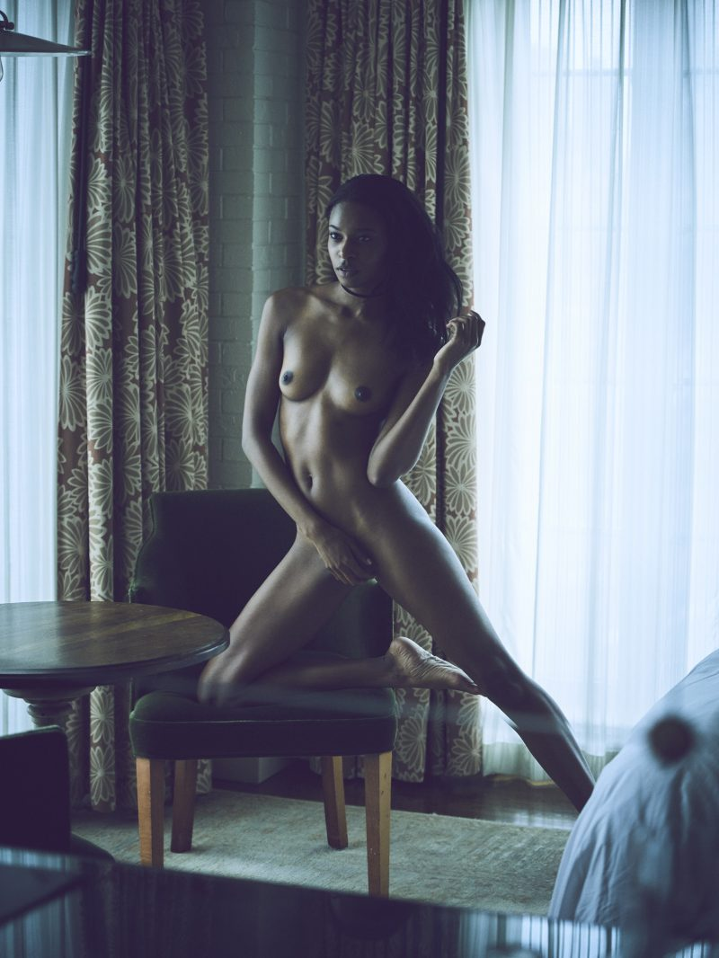 Naked black girl with one knee on table in hotel room by Stefan Rappo