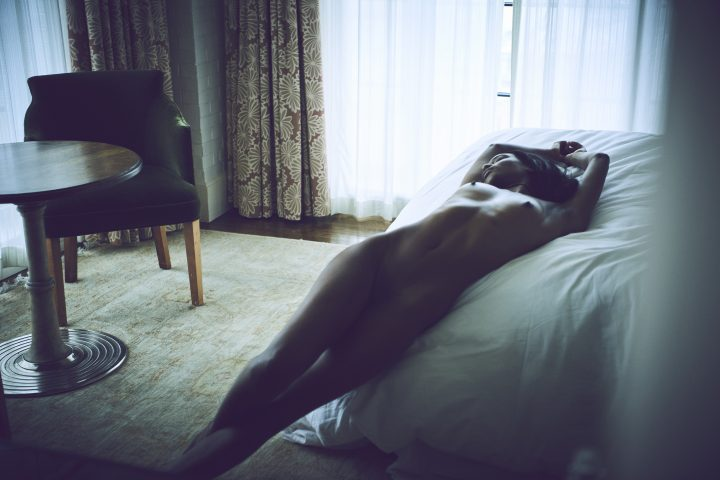 Naked black girl lying on bed in hotel room by Stefan Rappo