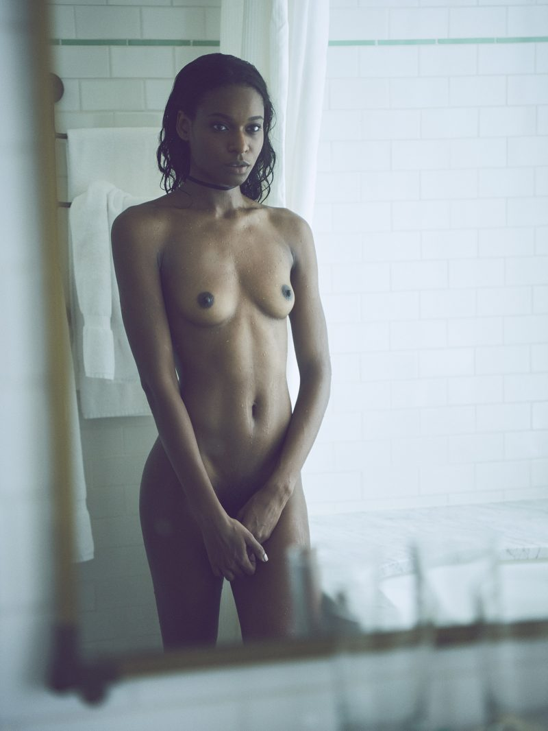 Naked black girl looking at herself in mirror in bathroom by Stefan Rappo