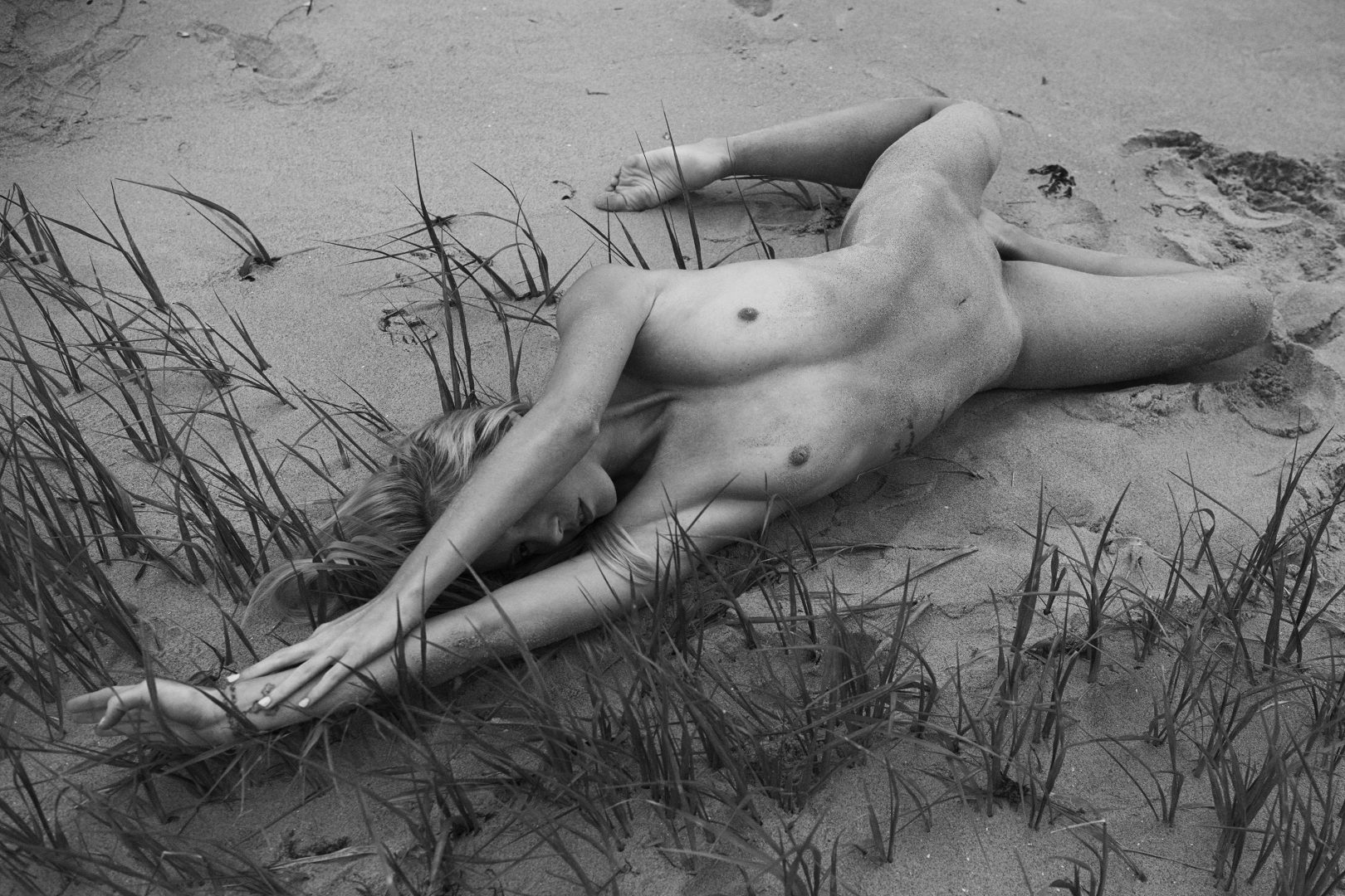 Naked girl lying on the beach between grass by Stefan Rappo