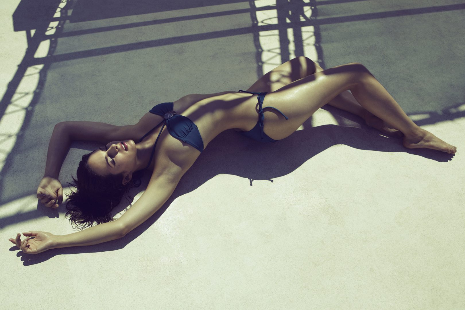 Girl lying on floor in swimsuit by Stefan Rappo