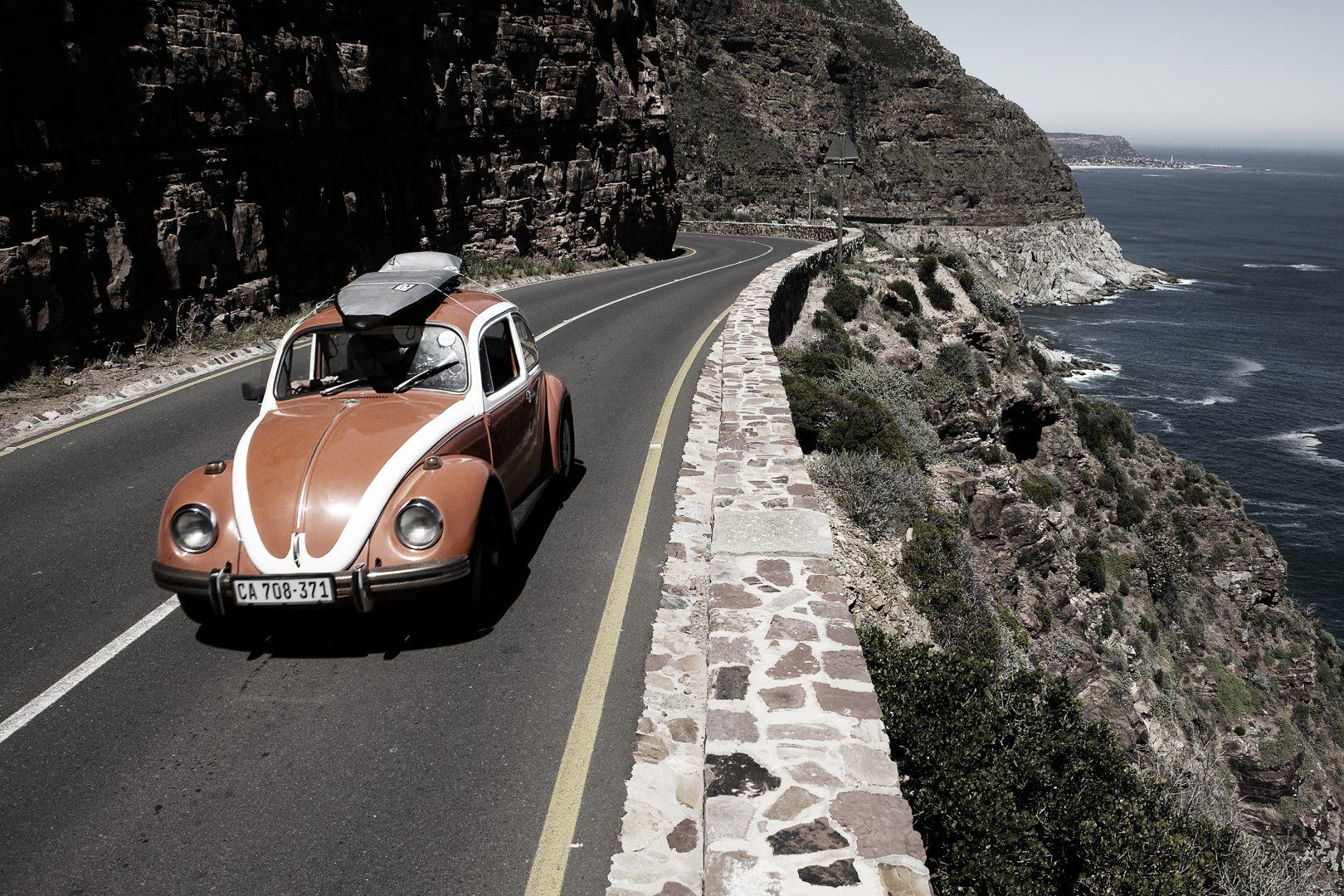 Beatle car with surfboard on roof by Stefan Rappo