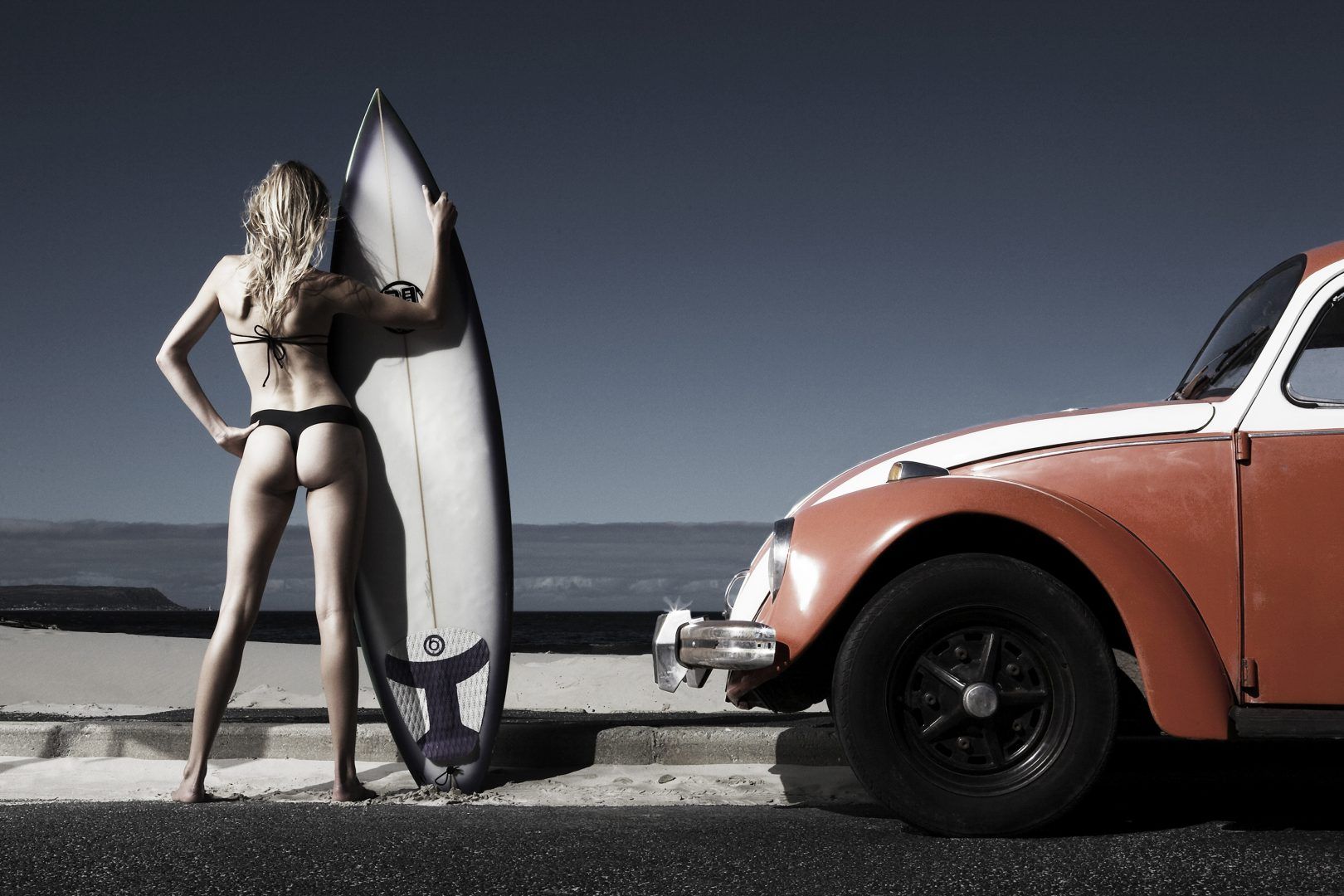 Girl in swimsuit standing next to beatle car with surfboard by Stefan Rappo