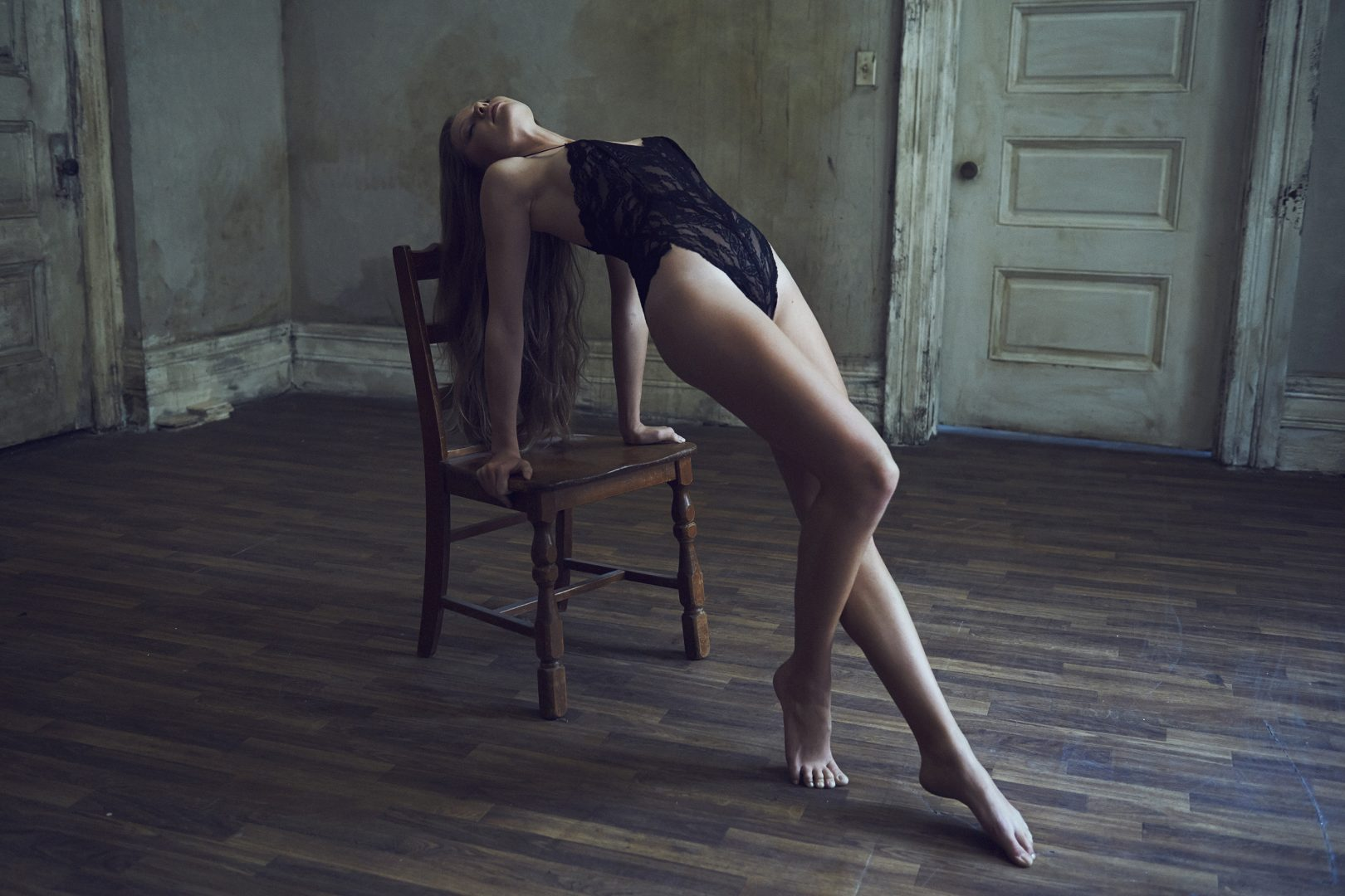 Girl in lingerie leaning on chair by Stefan Rappo