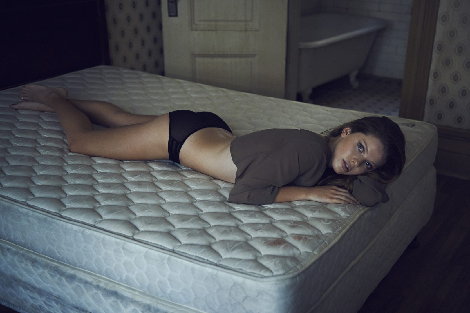 Girl on lingerie lying on bed in old hotel room by Stefan Rappo