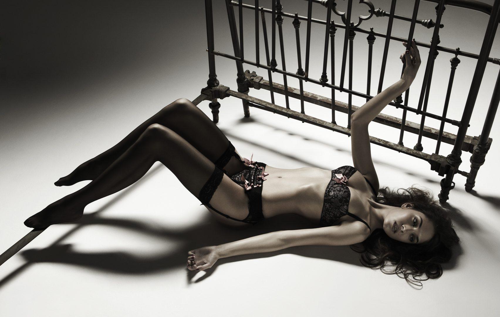 Girl in lingerie lying on floor by Stefan Rappo