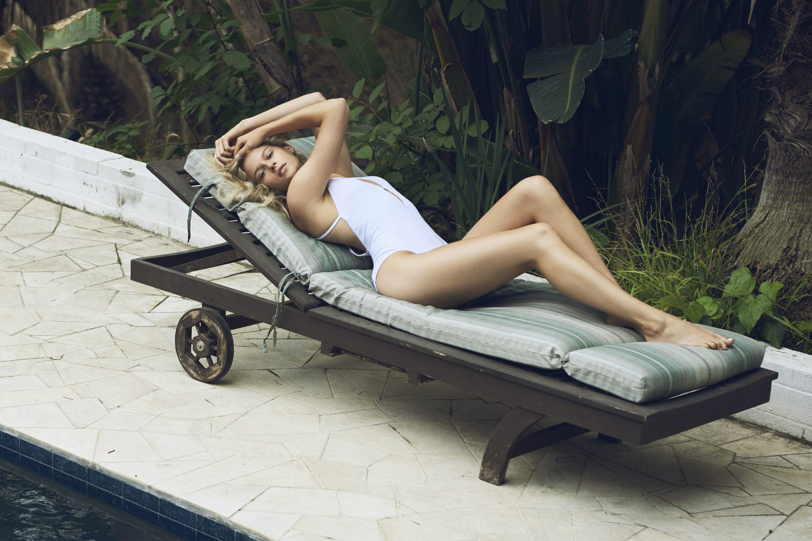 Girl lying on long chair in swimsuit by Stefan Rappo