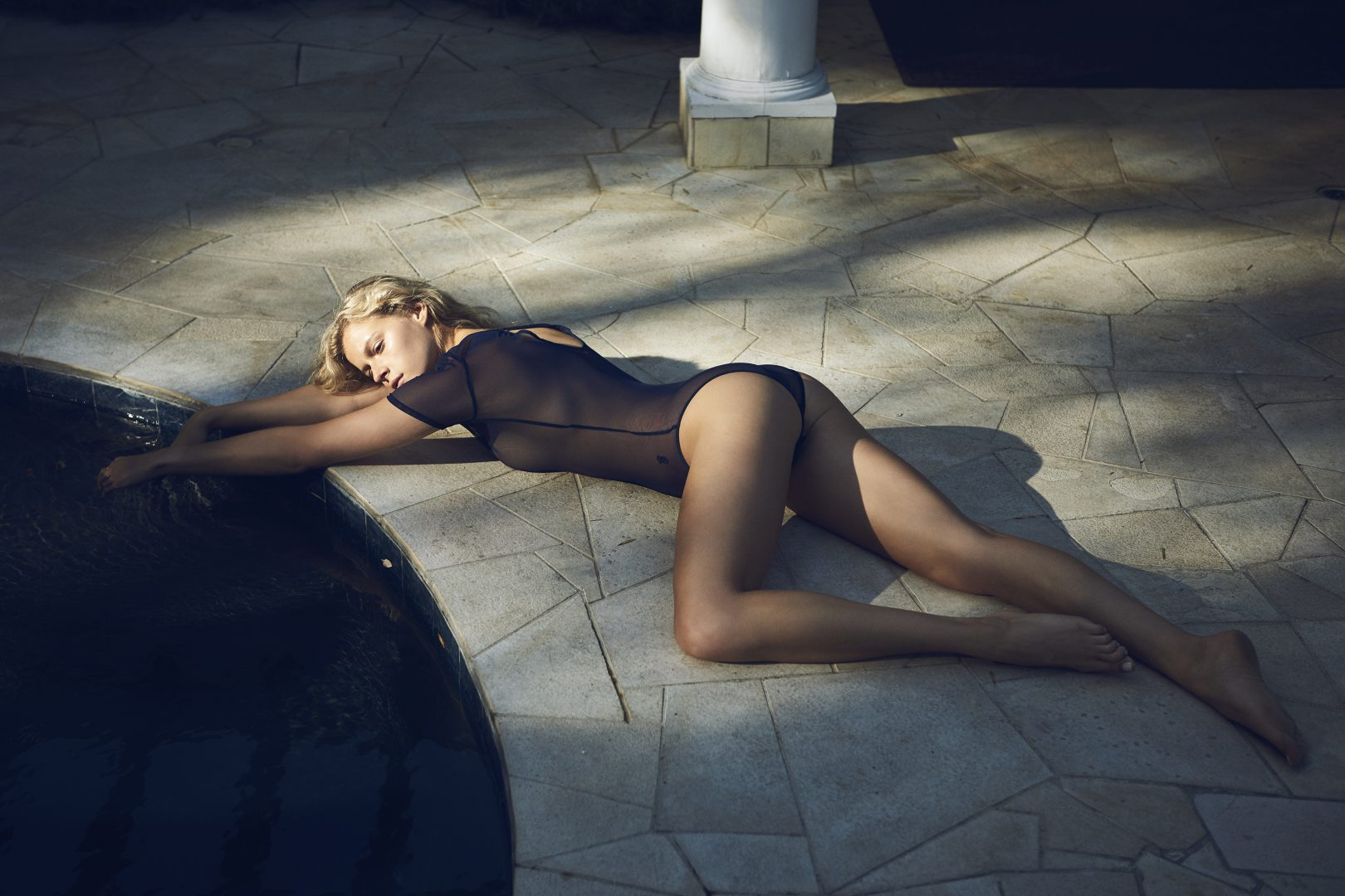 Girl lying in floor by pool in swimsuit by Stefan Rappo