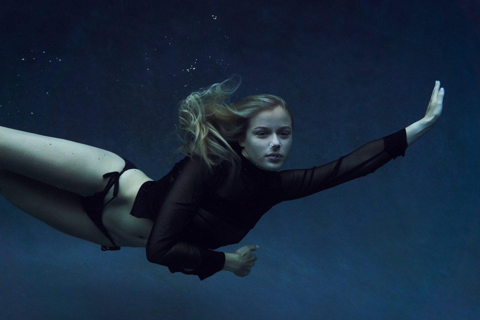 Girl diving in pool in swimsuit by Stefan Rappo