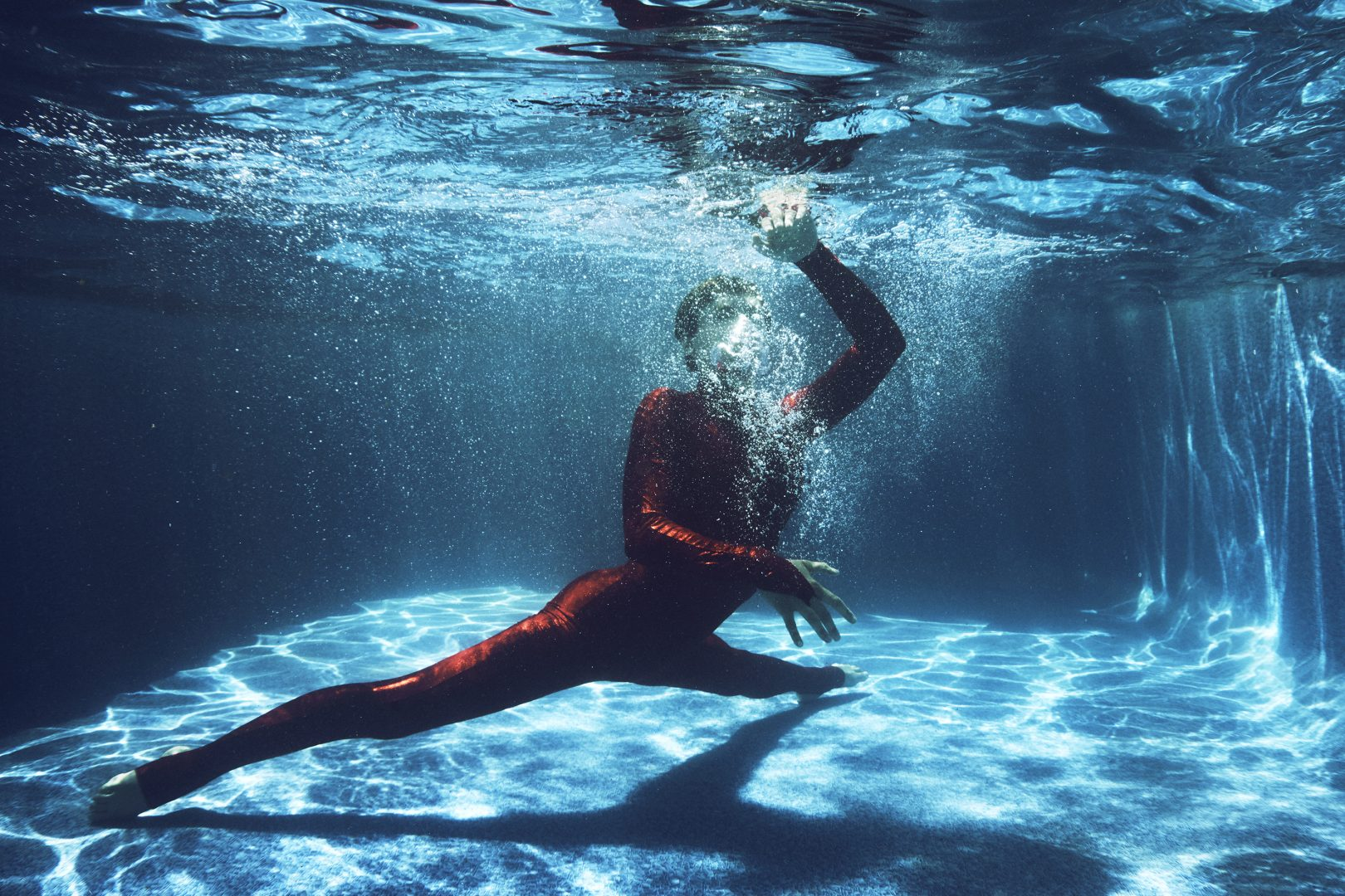 Contorsionist in red dress in swimming pool by Stefan Rappo