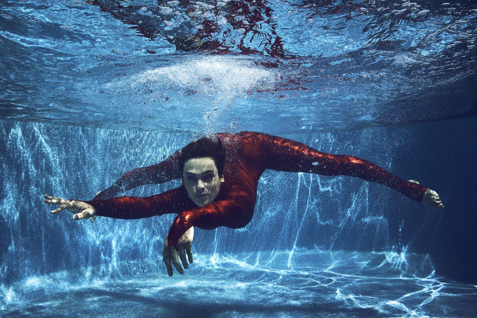 Contorsionist in red dress in swimming pool by Stefan Rappo