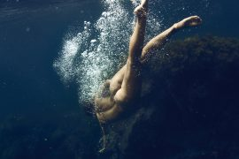 Thumbnail Naked girl twisting her body under water in sea by Stefan Rappo