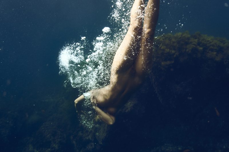 Naked girl twisting her body under water in sea by Stefan Rappo
