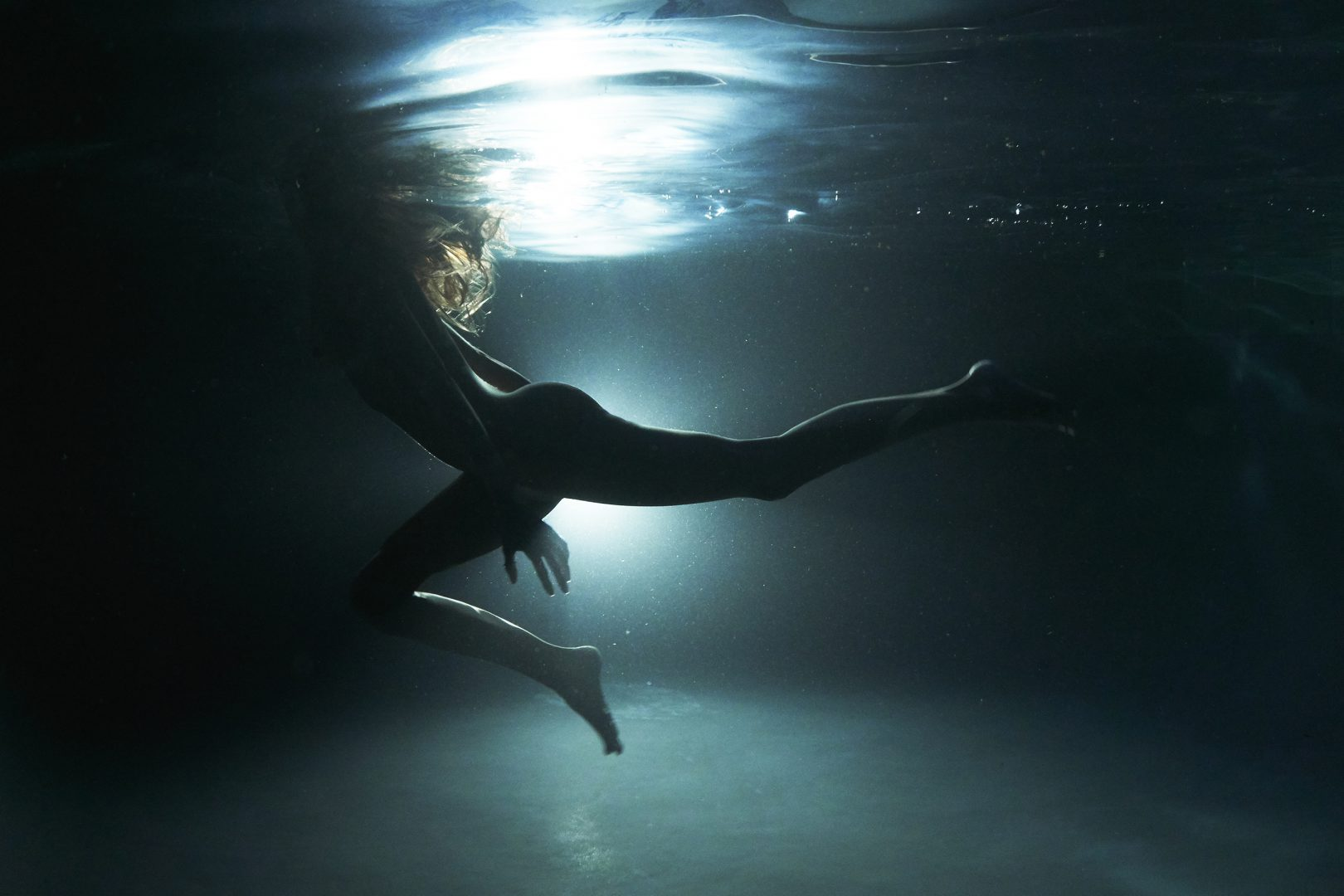 naked girl in underwater in swimming pool by stefan rappo