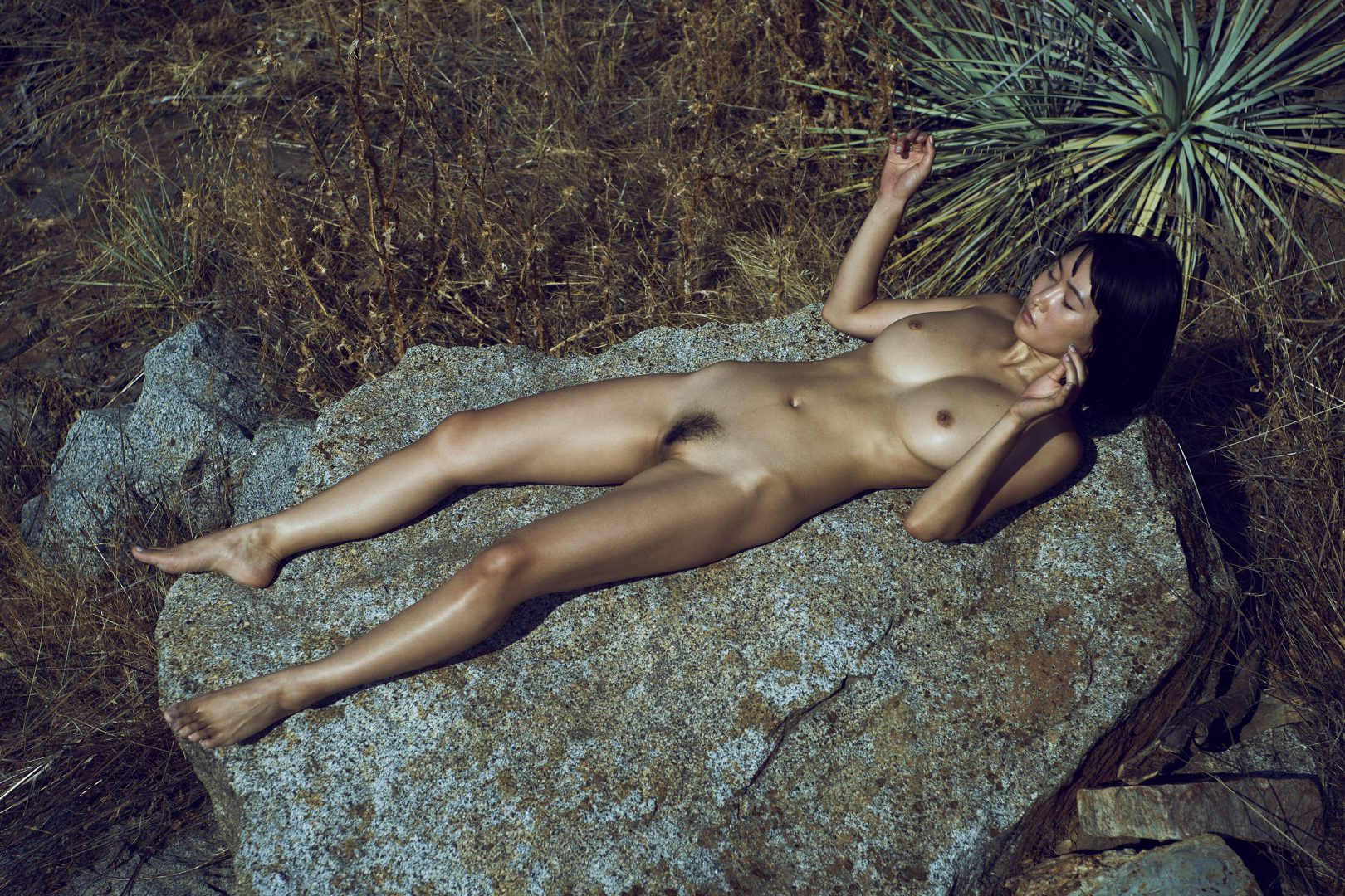 naked girl lying on rock close to river by stefan rappo