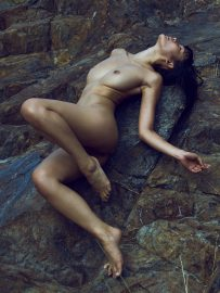 Thumbnail naked girl lying on rock close to river by stefan rappo