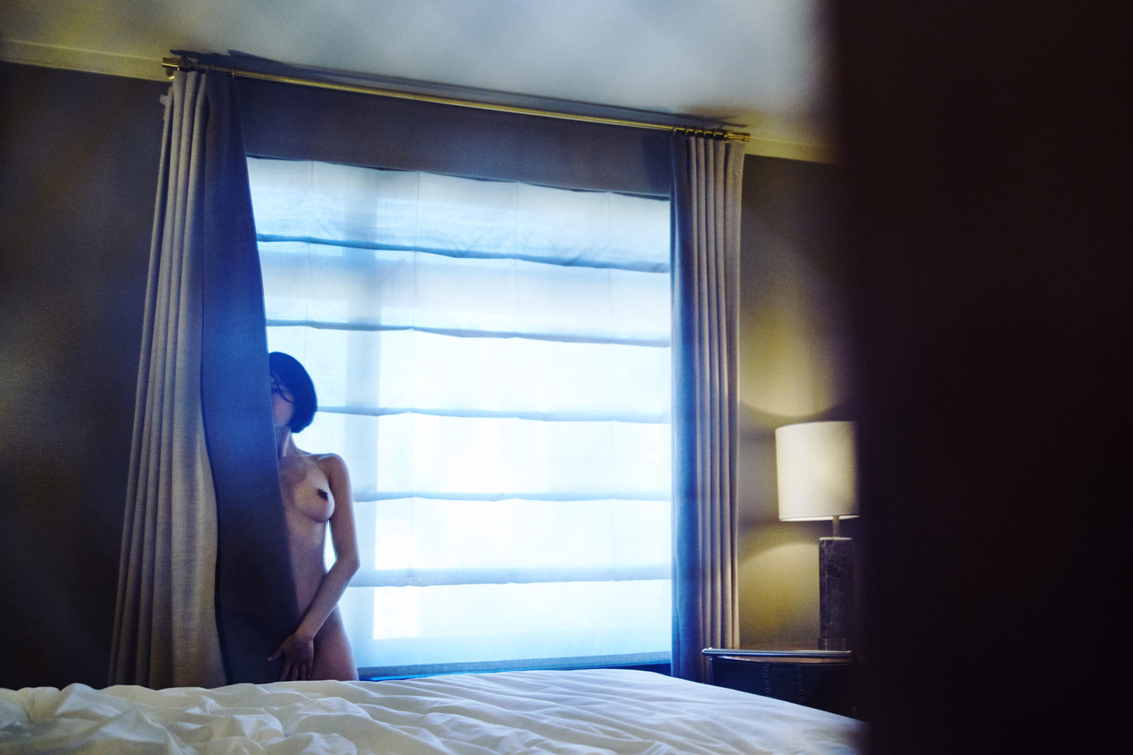 girl behind curtain in hotel room
