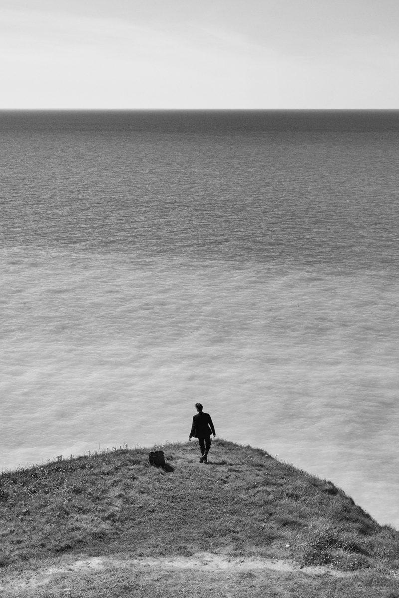 man standing on cliff by Stefan Rappo